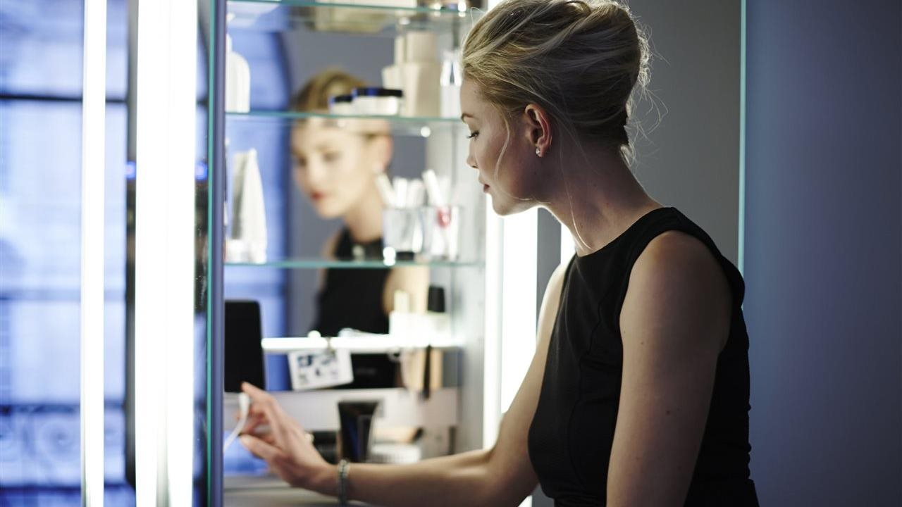woman standing at mirror in the bathroom checking her phone charge function