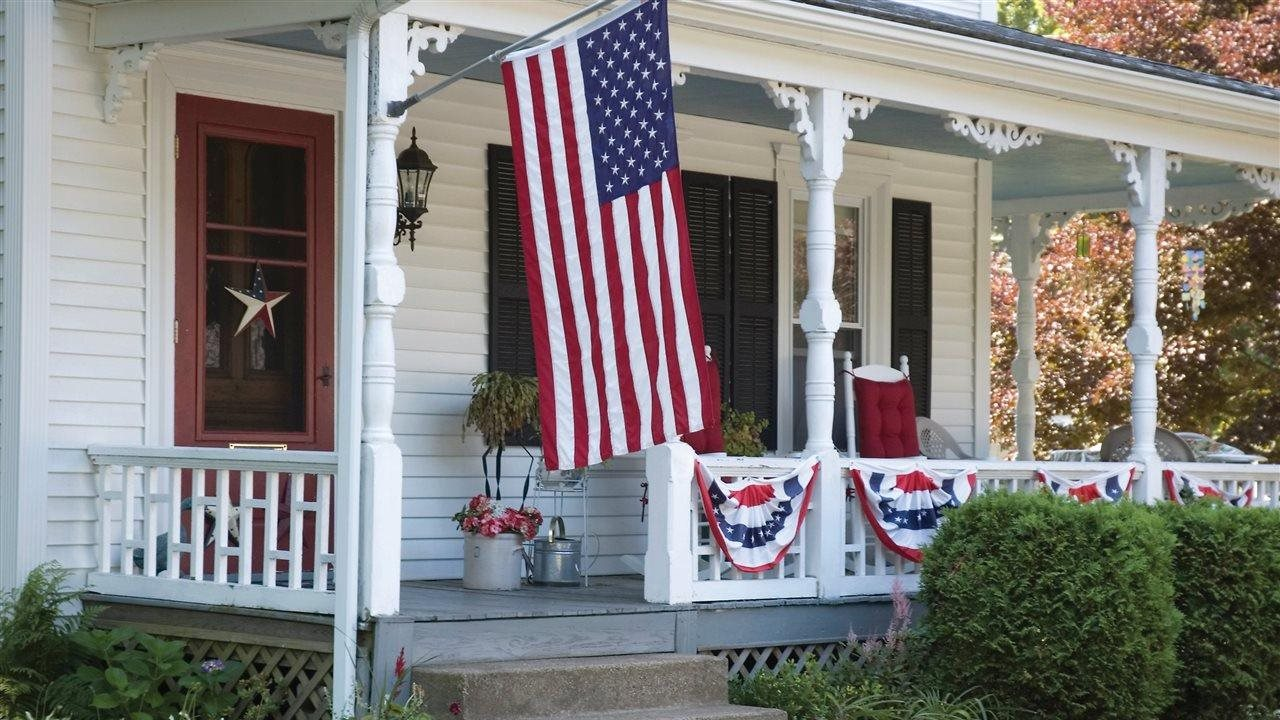 flag and other festive items on a front porch of a house