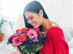 woman enjoyng flowers in a vase
