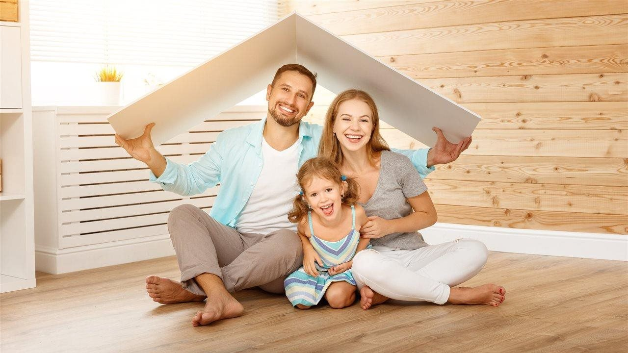 family sitting under two boards that look like a roof