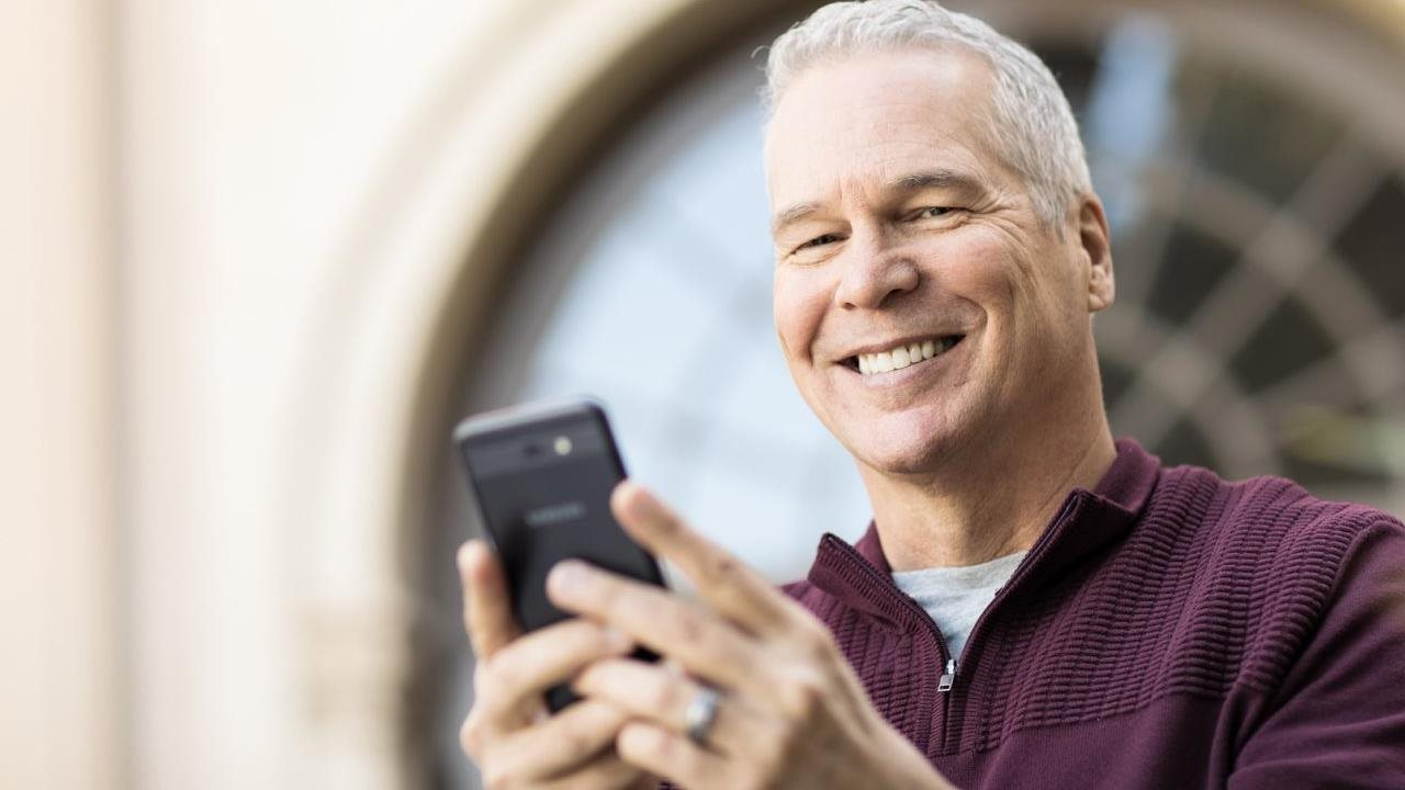 man outside smiling and using an older smart phone.