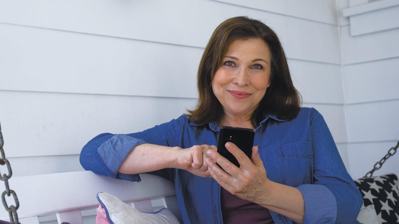 woman sittting on pourch using her cell phone