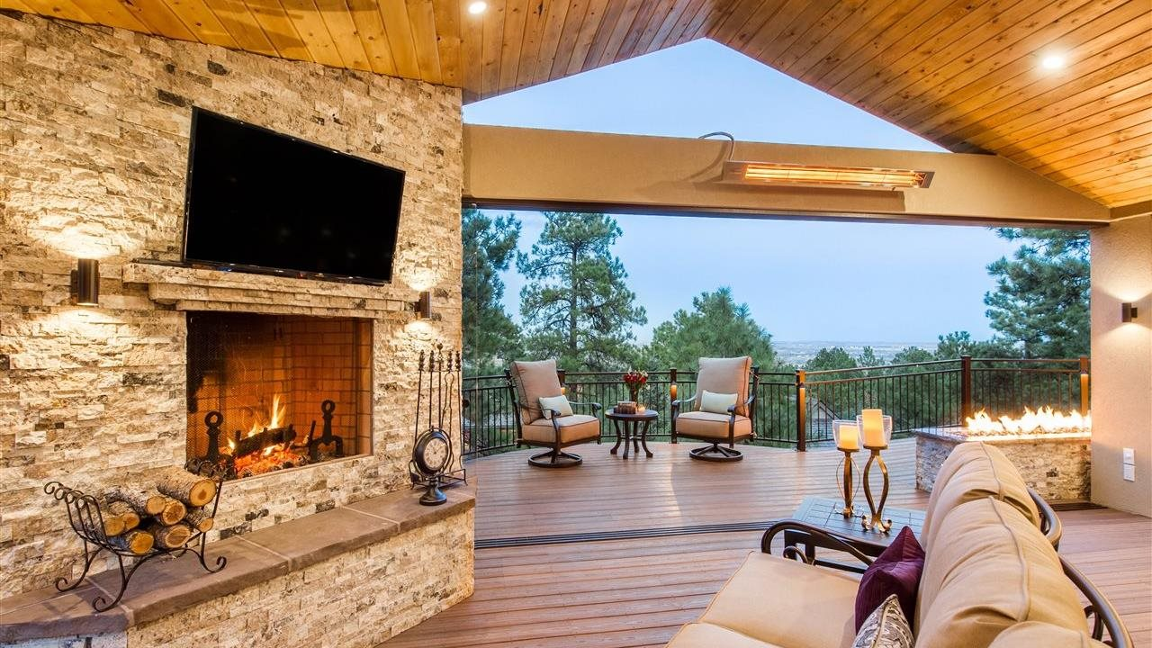 Year round outdooring living space with Tamko decking, fire place, comfortable furniture