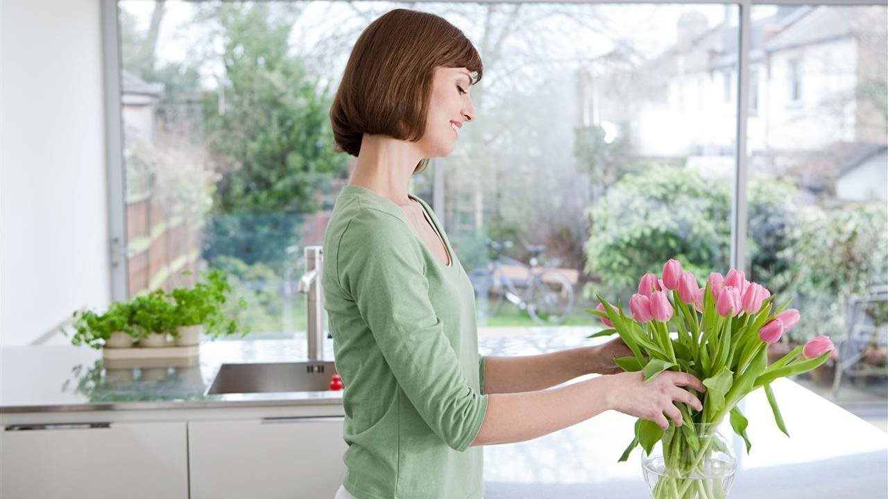 Woman arranging flowers in a kitchen