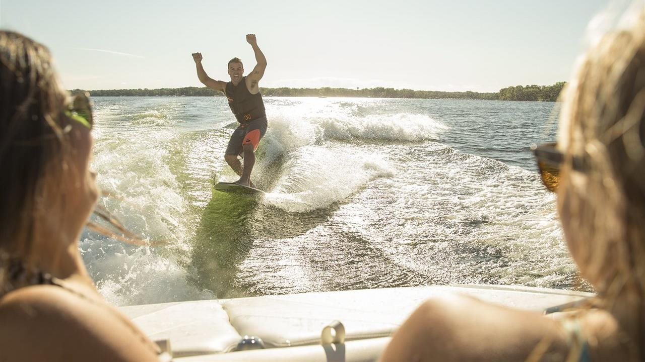 man wake boarding off the back of a boat with friends watching on board.