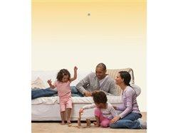 family in a living room with a sprinkler over their heads