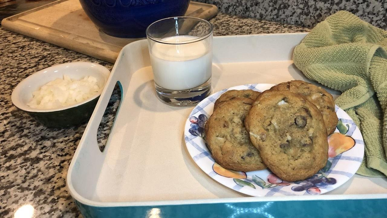 chocolate chip cookies on a plate on a tray with a glass of milk