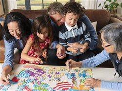 Family putting a puzzle together in the living room