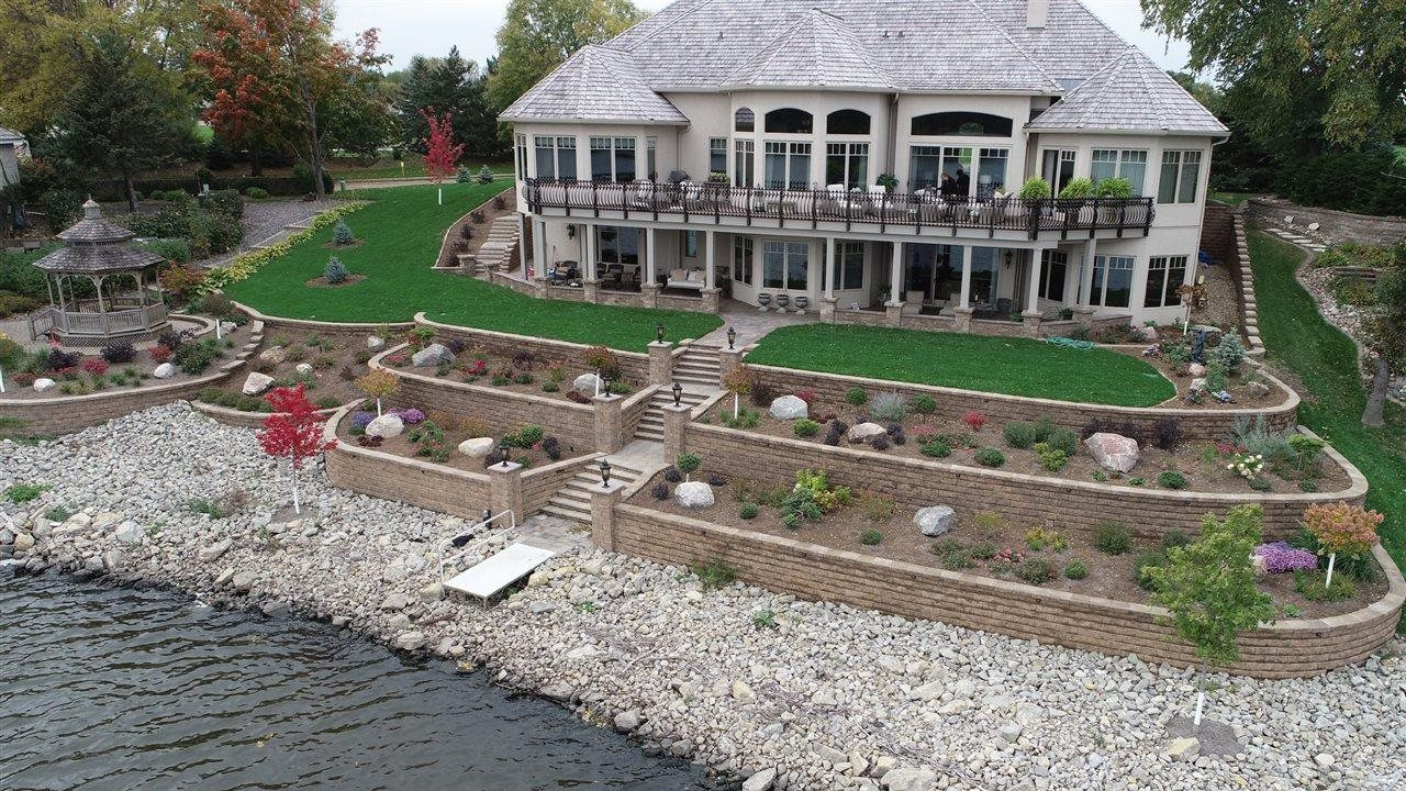 Huge lake home with retaining wall, step risers, seat wall, plantings and gazebo.