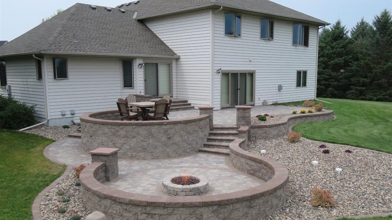 Retaining wall used in back yard with curved seat walled fire pit.