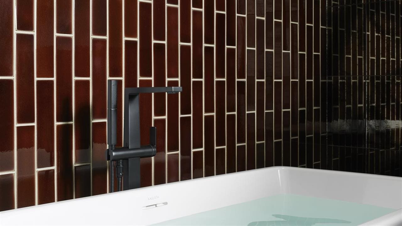 tub in bath with vertical subway tiles and inventive faucet