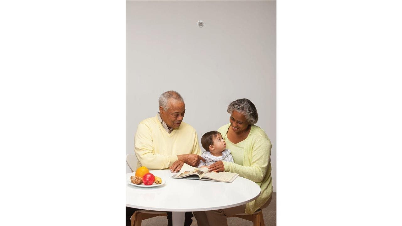 Grandparents talking with baby at table