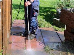 man power washing a patio