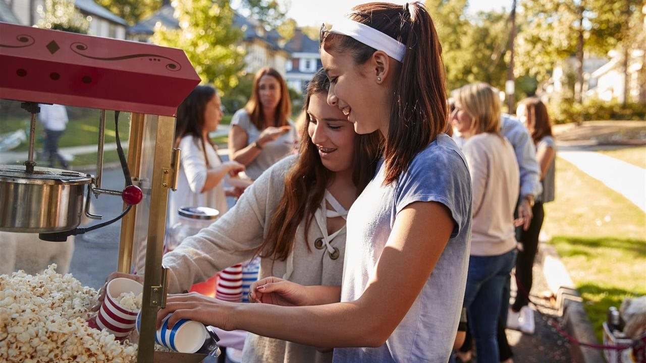 kids getting popcprn from an outdoor popcorn maker