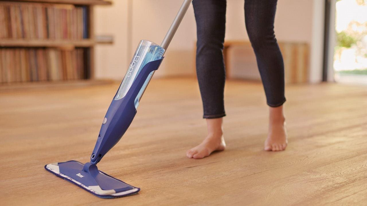 woman cleaning the wood floor with bona