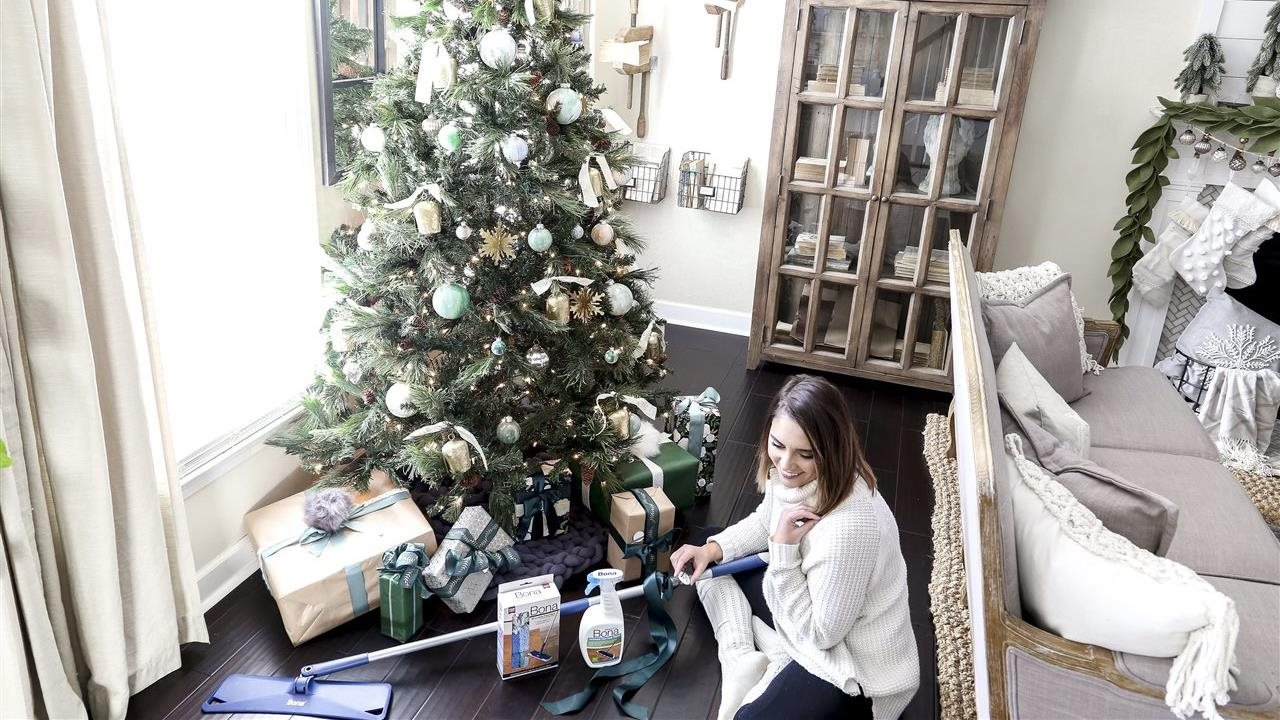 woman assembling bona floor cleaner next ro Christmas tree in living room