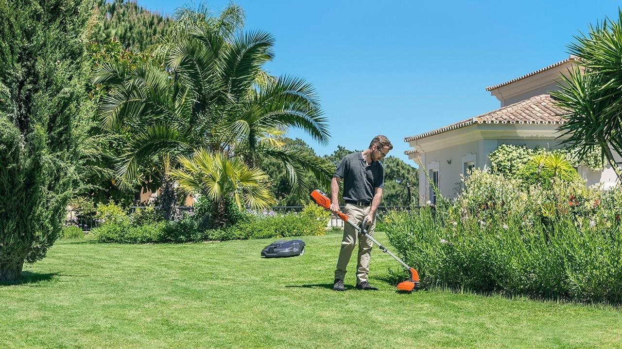 man trimming landscaping in his backyard