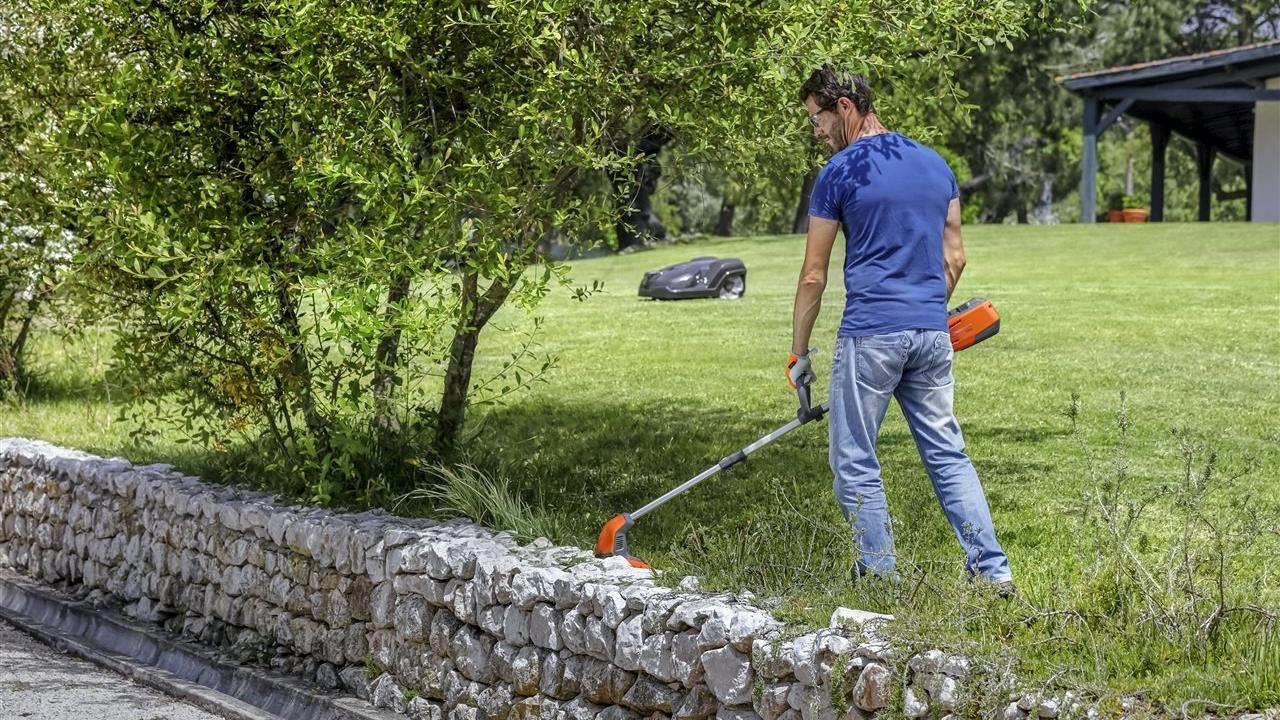 man using grass trimmer along a retaining wall