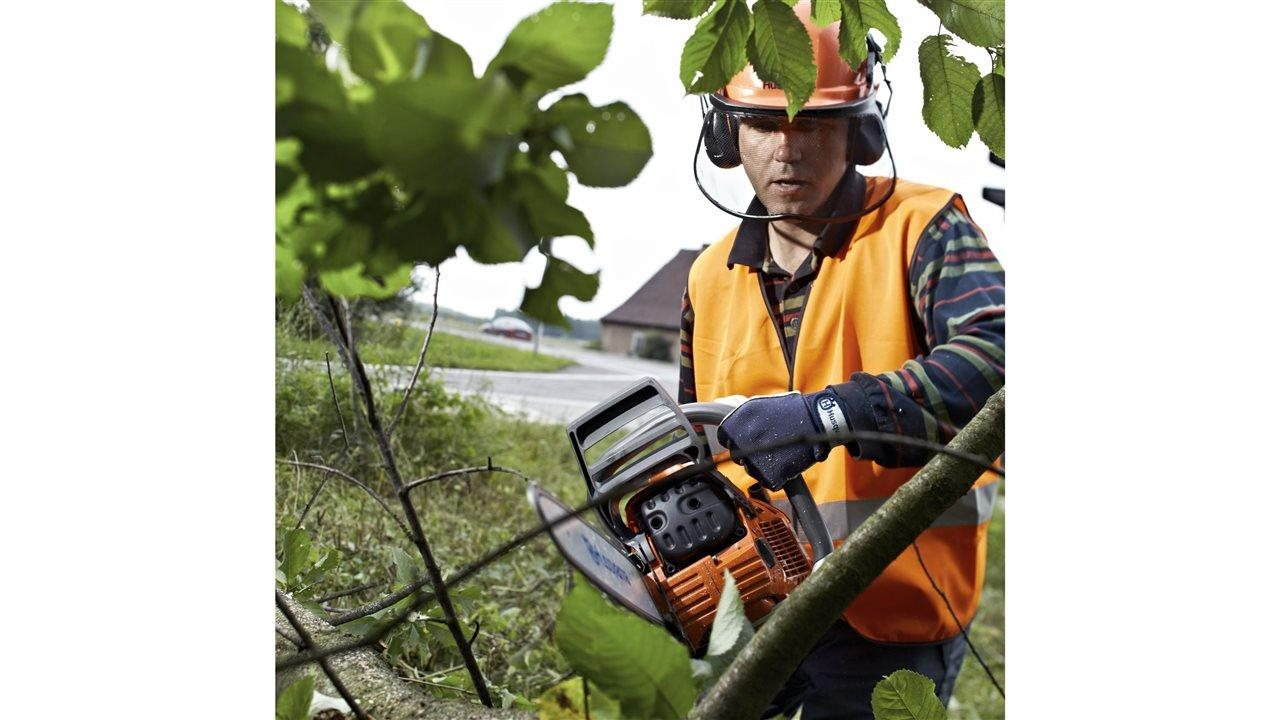 man using Husqvarna chain saw to cut tree limb