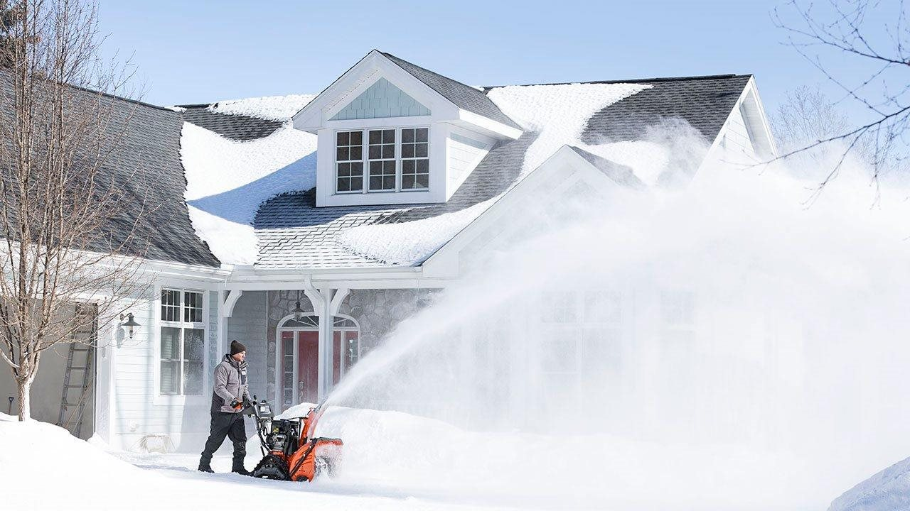man using snowblower on driveway in front of snow covered house