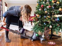 woman vacuuming under a Christmas tree