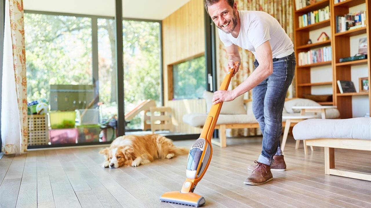 man vacuuming the floor with his dog taking a nap near by