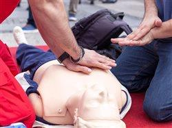 Person teaching another CPR using a doll