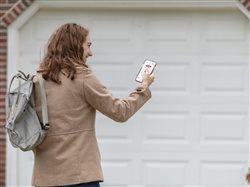 woman with smart phone opening garage door