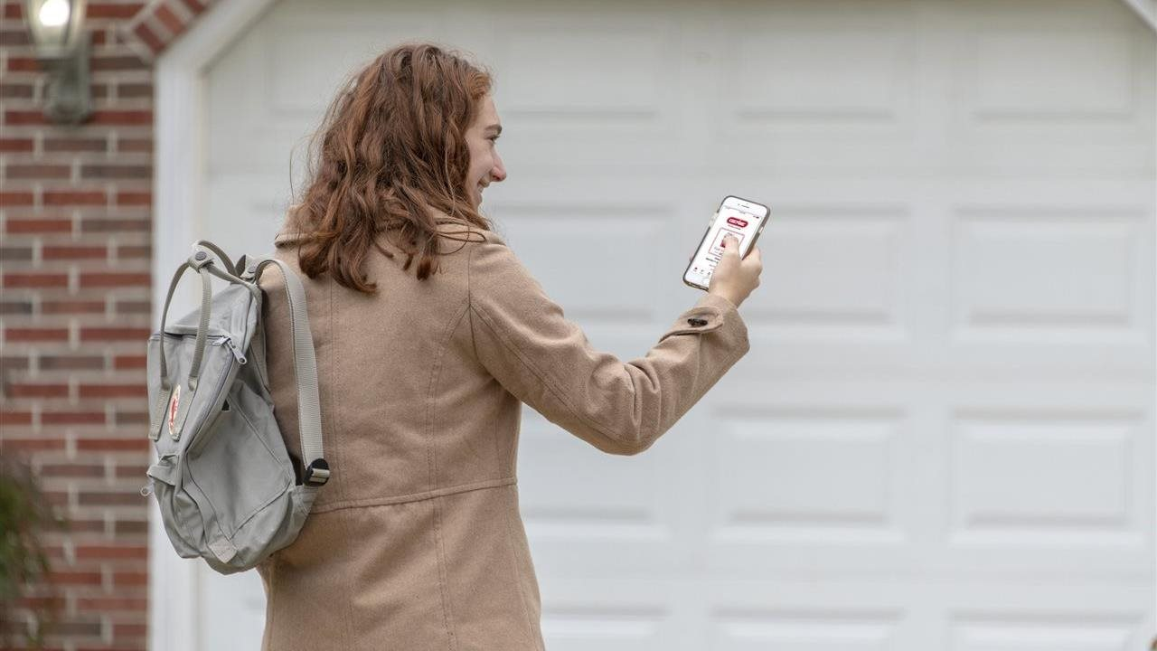 woman with smart phone opening garage door