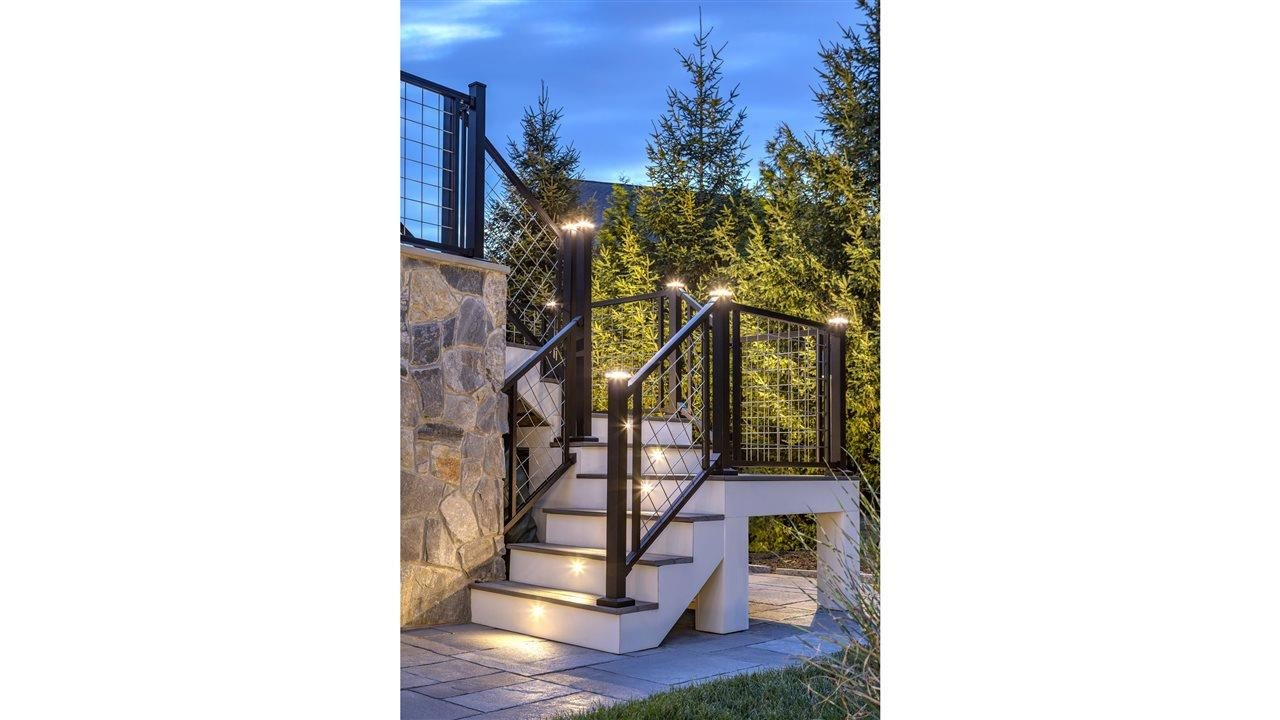 Beautiful lighting on stair railing coming down from a deck