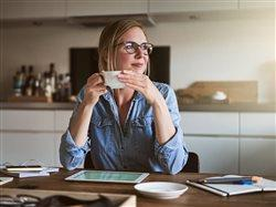 A pensive woman wearing glasses and sitting at her kitchen table with a tablet is enjoying cup of coffee.