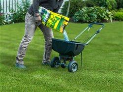 man pouring preen one in a lawn spreader