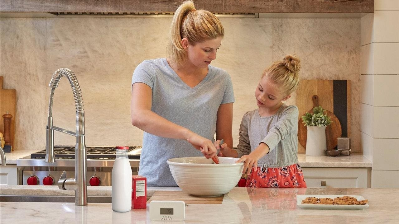 little girl and her mother making cookies in the kitchen with a carbon monoxide alarm on the counter
