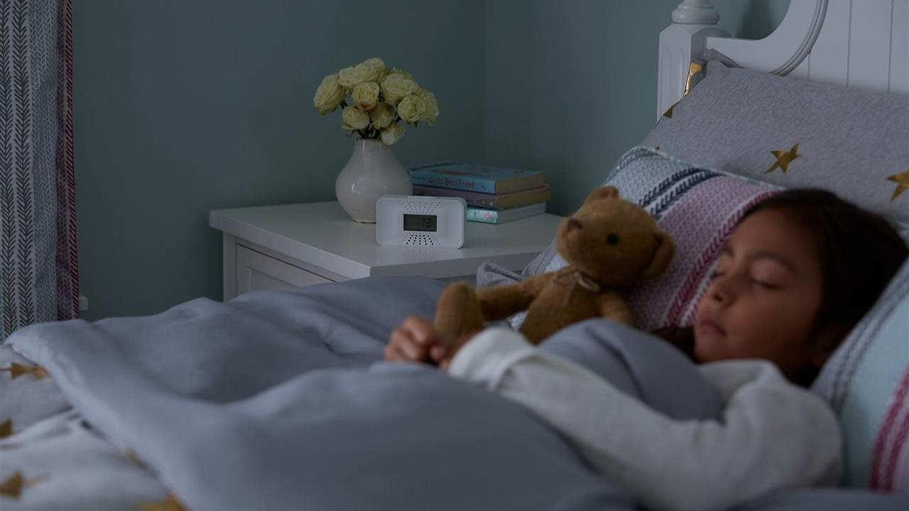 Little girl resting easy in her bed with a teddy bear and carbon monoxide alarm on her night stand