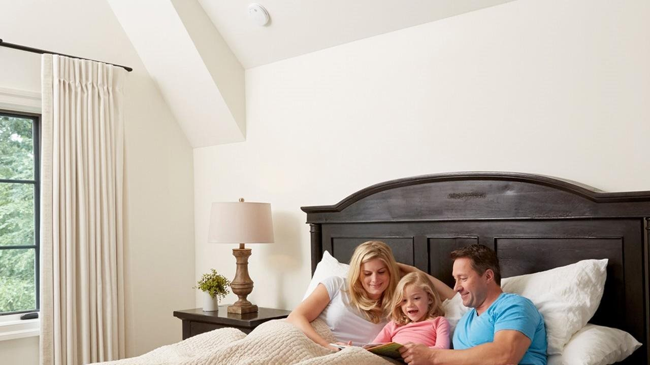 first alert on ceiling over bed where parents are reading a story to their daughter