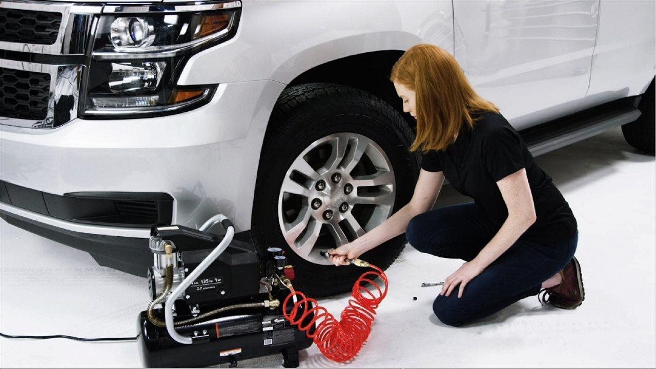 woman filling a car tire with air