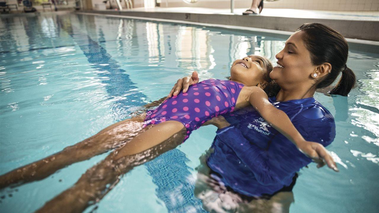 Instructor teaching child how to swim