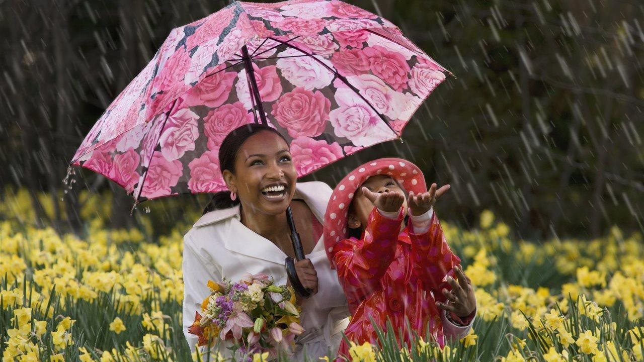 mom and daughter under umbrella and playing in the rain