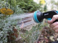 person wqater an herb garden with a water sprayer