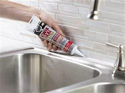 person sealing backsplash near kitchen sink