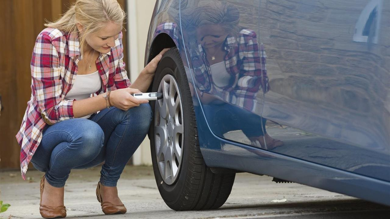 woman checking air pressure of tires on car