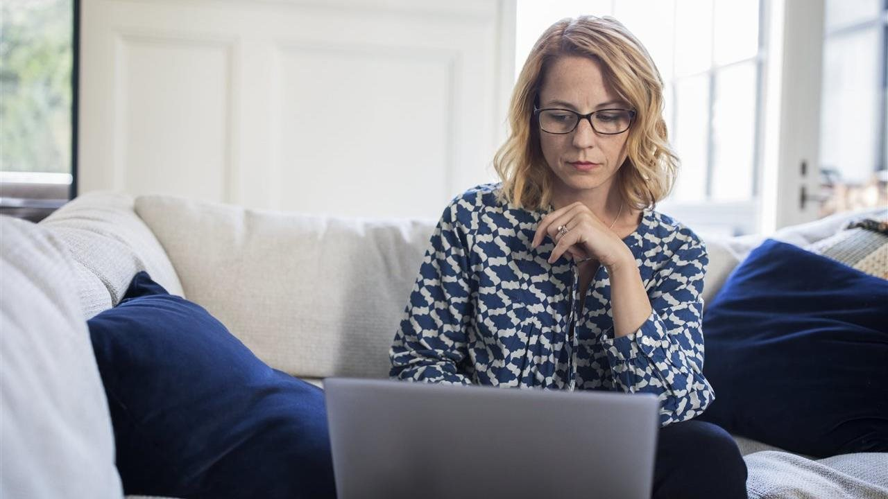 woman working on laptop while on sofa ant home
