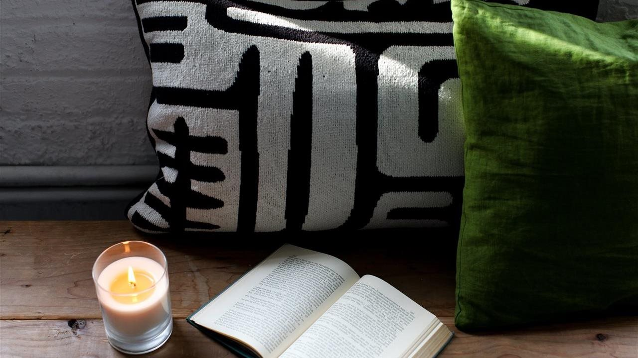 Glowing candle near a book and cozy pillows
