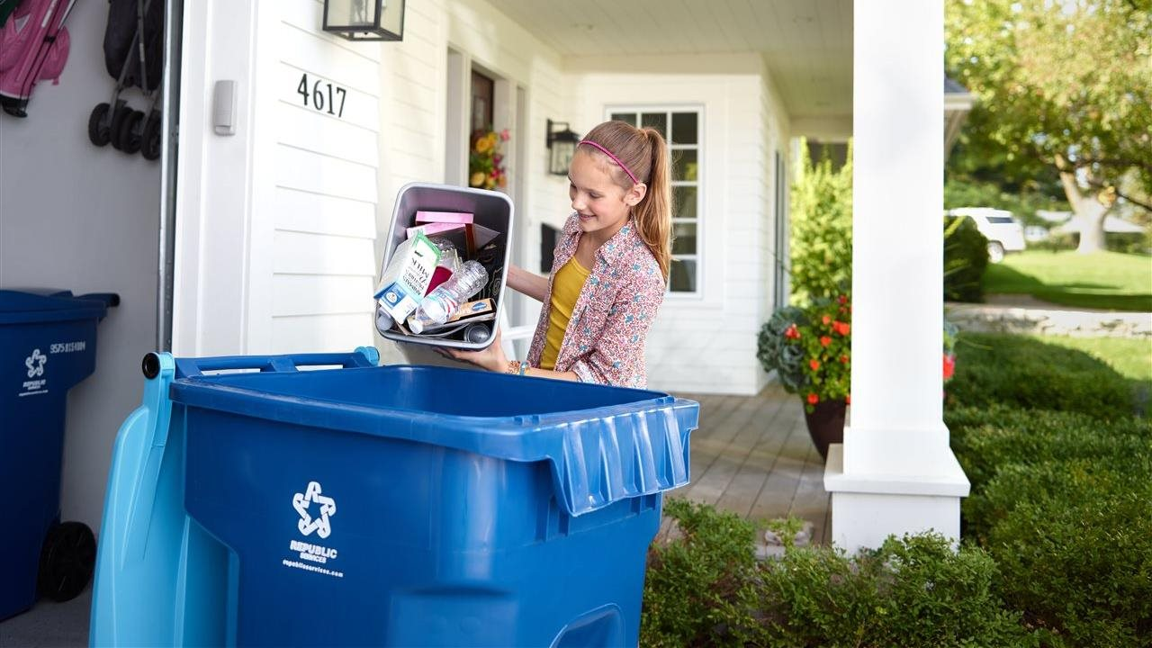 Teen girl dump recycling into a recycling bin in front of a garage.