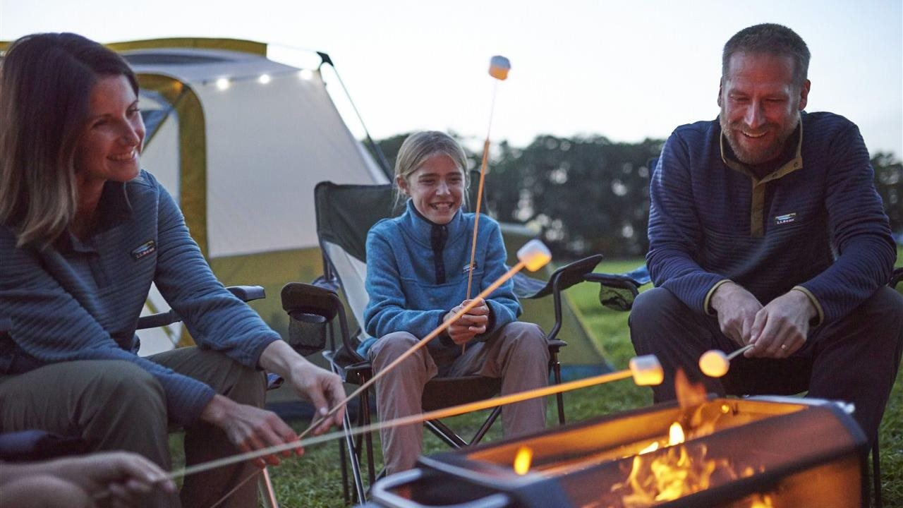 family camping a toasting marshmallows over a fire