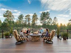 family sitting in patio chairs around a raised fire pit on their huge deck in their beautiful back yard