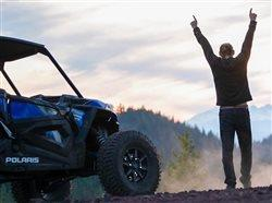 victorius person celebrating next to a polaris UTV