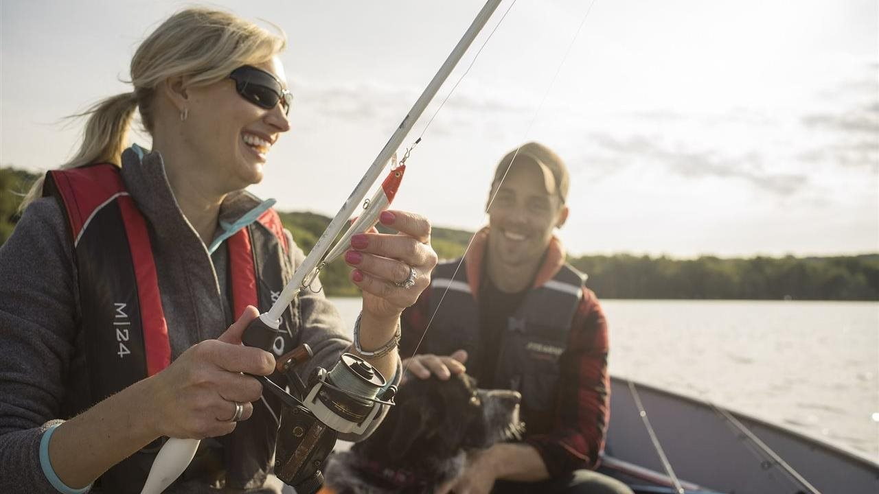 woman fishiing in a boat with a man and a dog