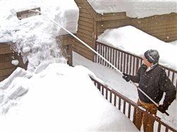 man knocking snow off of the roof of a house with a snow rake