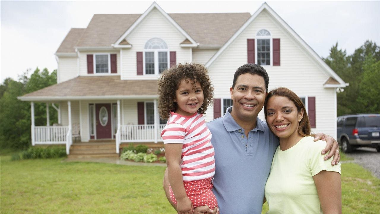 family standing in front of their new home